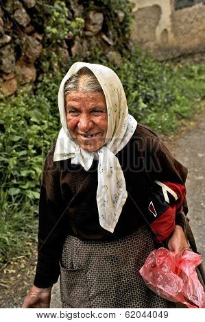 An old Macedonian lady walking up the street with a bucket in her hand in the countryside of Ohrid.