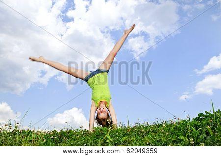 Young teenage girl doing cartwheel in a summer meadow