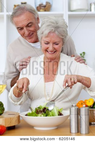 Happy Senior Couple Eeating A Salad In The Kitchen