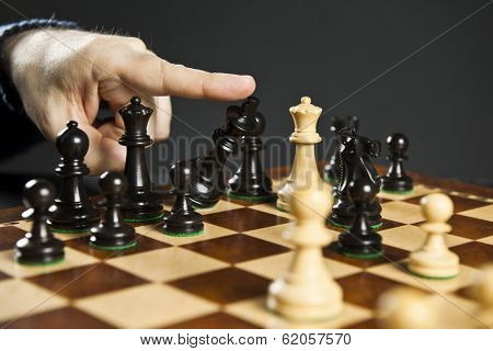 Finger pushing over King chess piece in defeat