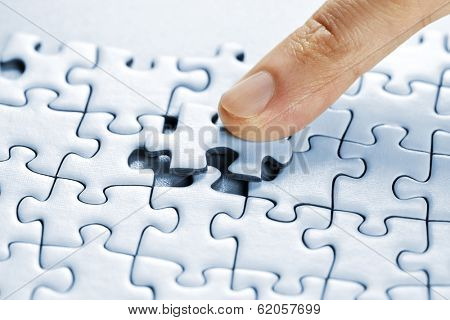 Finger pushing missing puzzle piece into place