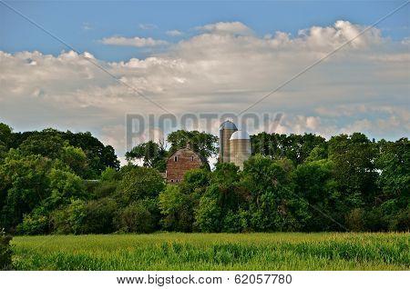 Farm site on hill above corn field