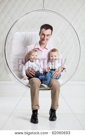 Father with two babies on swinging hanging chair