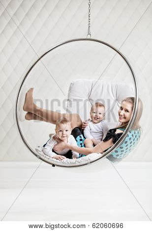 Woman with two babies on swinging hanging chair