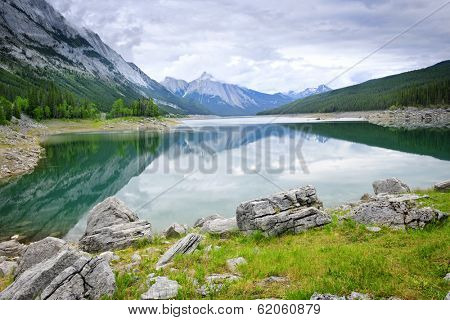 Mountains reflecting in Medicine Lake in Jasper National Park, Canada