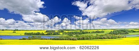 Panoramic landscape prairie view of canola field and lake in Saskatchewan, Canada