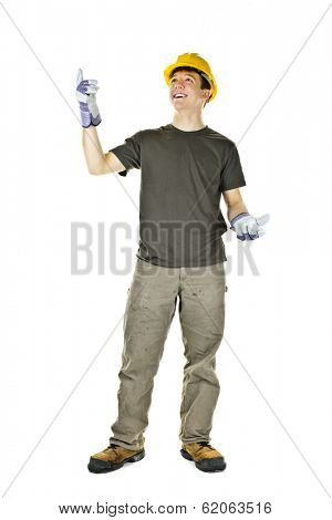 Smiling construction worker pointing up standing isolated on white background