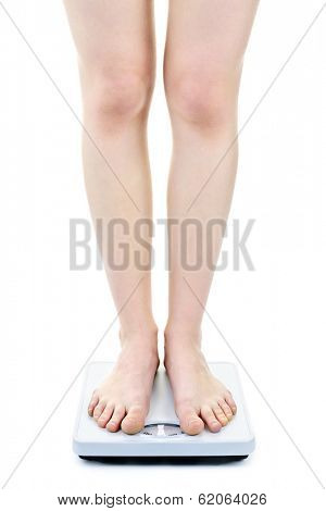 Slender female legs standing on bathroom scale