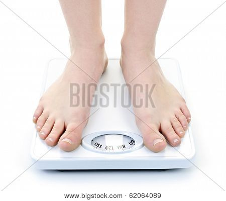 Bare female feet standing on bathroom scale