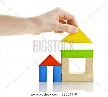 Wooden block houses under construction isolated on white background