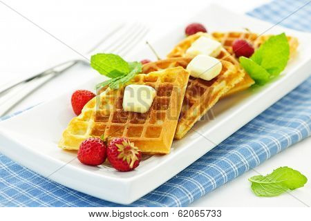 Plate of belgian waffles with fresh strawberries and pats of butter