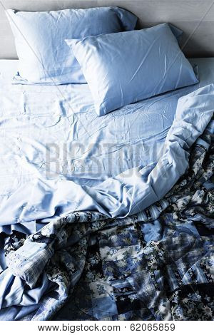 Unmade messy bed with wrinkled sheets from above