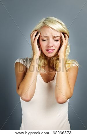 Upset young blonde woman with headache on grey background