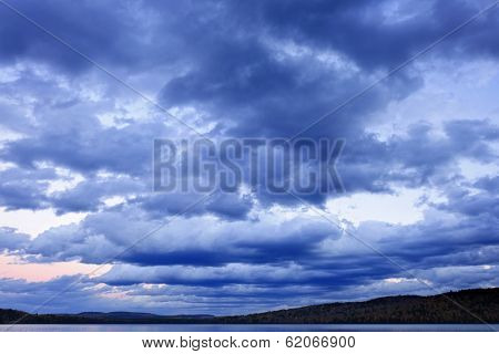 Blue cloudy dramatic sky at sunset over forest wilderness in Algonquin Park, Canada