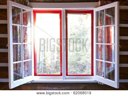 Open windows in cottage with sunshine and view of forest