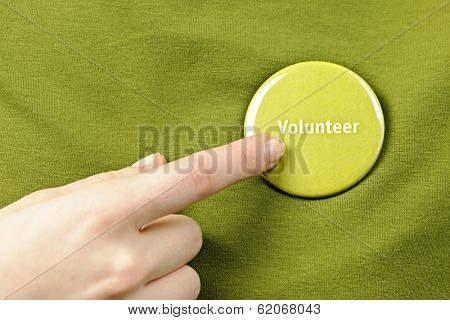 Finger pointing to green round volunteer button