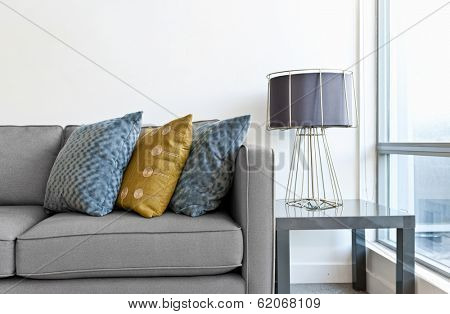 Interior design with couch, colorful cushions and lamp on end table