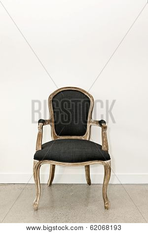 Antique upholstered armchair furniture against white wall