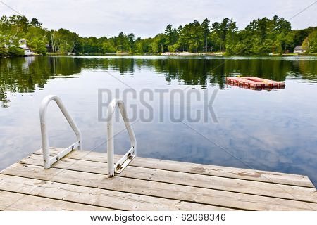 Dock and ladder on summer lake with diving platform in Ontario Canada