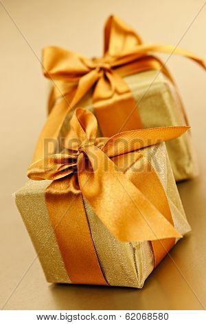 Two gift boxes in gold wrapping paper with ribbon and bow