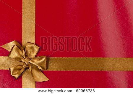 Red background of present wrapped with gold satin ribbon and bow