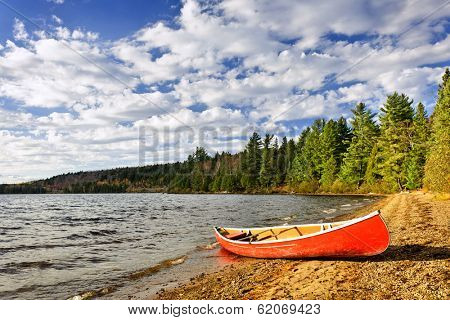 Red canoe on beach at Lake of Two Rivers, Ontario, Canada