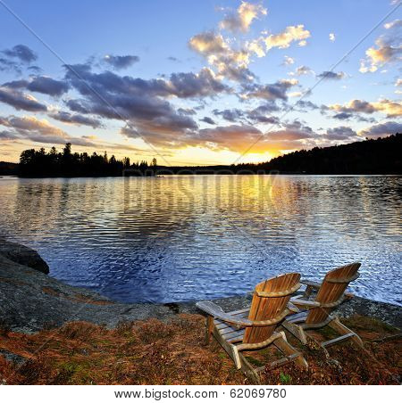 Wooden chair on beach of relaxing lake at sunset in Algonquin Park, Canada