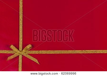 Red background of present wrapped with gold ribbon and bow
