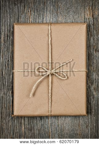 Gift package in brown paper wrapper tied with string on rustic wood background