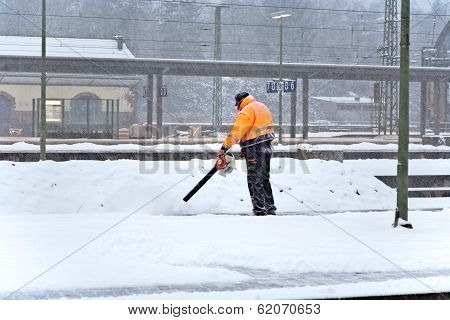 Worker Is Cleaning The Platform Of A Train Station From Snow