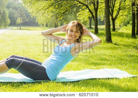 Female fitness instructor exercising doing sit-ups on yoga mat outside in green summer park