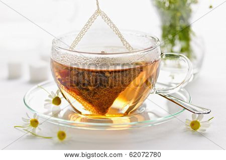 Glass teacup with soothing herbal tea in silk bag