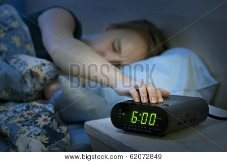 Young woman pressing snooze button on early morning digital alarm clock radio