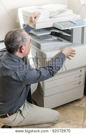 Business man opening photocopy machine in office