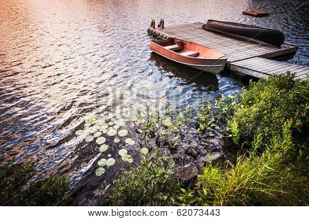 Sunset reflecting in lake water with rowboat tied to wooden dock at rocky shore. Ontario, Canada.