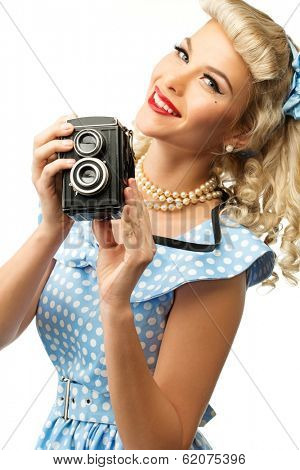 Blond coquette pin up style young woman in blue dress with vintage camera