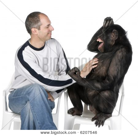 Portrait Of Mid Adult Man Tickling Chimpanzee