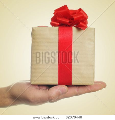 a man hand holding a gift with a red ribbon on a beige background, with a retro effect