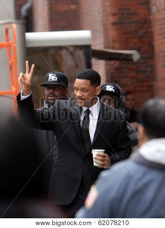NEW YORK CITY - APRIL 15: Actor Will Smith, carrying a coffee cup, gives the peace symbol to some fans while working on the set of
