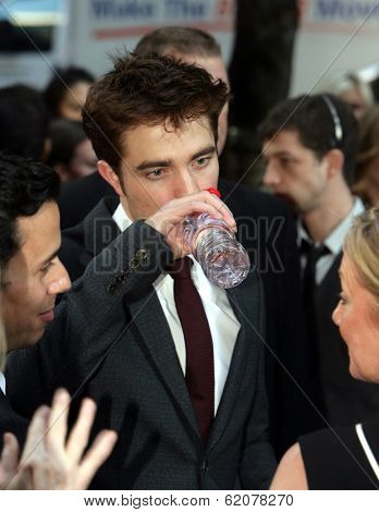 NEW YORK CITY - APRIL 17: Robert Pattinson grabs a drink of Evian bottled water at the worldwide premiere of 20th Century Fox's