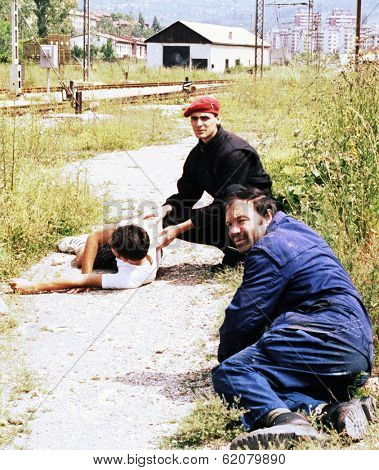 SARAJEVO, BOSNIA - JUNE 17: Two men duck for cover while trying to help another man critically injured by a sniper's bullet in a train yard in Sarajevo, Bosnia, on Thursday, June 17, 1993.