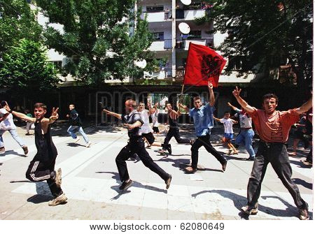 MITROVICA, KOSOVO - JULY 2: Angry Kosovar Albanians run through the streets on their way to a French army checkpoint separating their half of the city from ethnic Serbs in Mitrovica, Kosovo, on Friday, July 2, 1999.