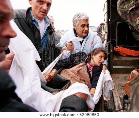 KOSOVO POLJE, KOSOVO, 1 JULY 1999 - A dazed and injured ethnic Albanian woman is comforted by British NATO after an attack by Kosovar Serbs in this ethnically divided city.