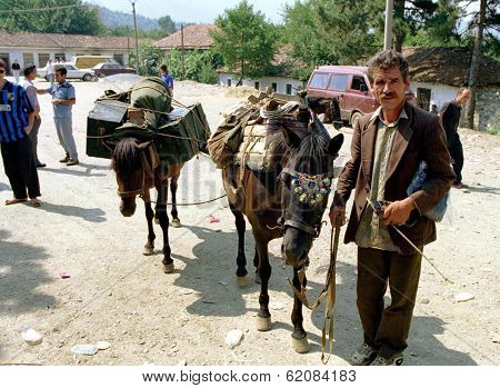 TROPOJE, KOSOVO, 19 JULY 1998 -- A Kosovo Liberation Army (UCK) smuggler brings weapons across the border from neighboring Albania using horses.