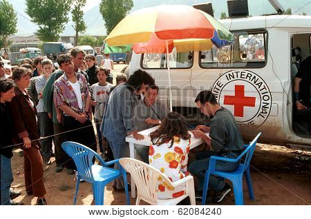 KUKES, ALBANIA, 18 APRIL 1999 --- Kosovar Albanian refugees line up to make satellite telephone calls at a mobile center set up by the International Committee of the Red Cross.