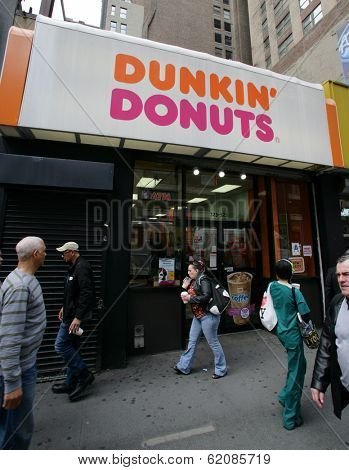 NEW YORK CITY - APRIL 19: Pedestrians walk past a Dunkin' Donuts franchise in New York City, on Friday, April 19, 2013.