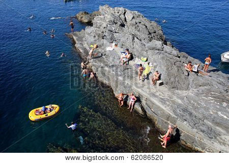 MANAROLA - ITALY: AUG 17: Bathers swim off the rocks in the marina of Manarola, Italy, on Sunday, August 17, 2013. The village is one of five towns of Cinque Terre.