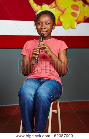 African girl learning to play music instrument in elementary school