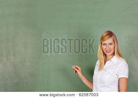 Teacher writing math problem on a chalkboard in elementary school