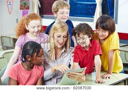 Teacher using digital media on tablet PC in elementary school class